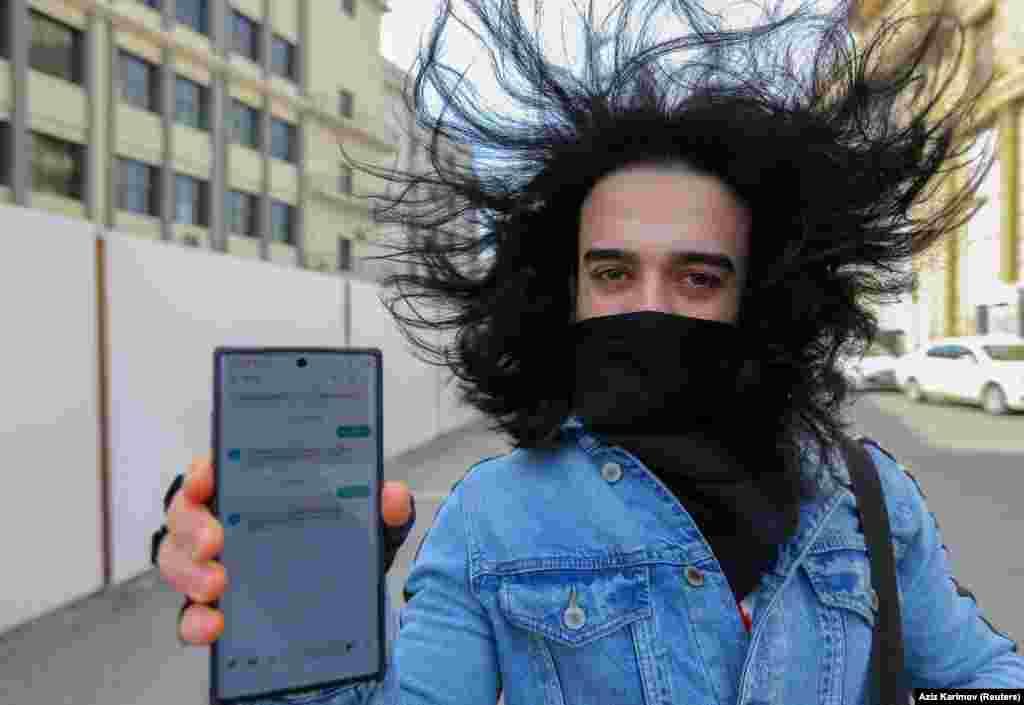 СМС арқылы үйінен шығуға рұқсат алған ер адам хабарламаны көрсетіп тұр. Баку, Әзербайжан.