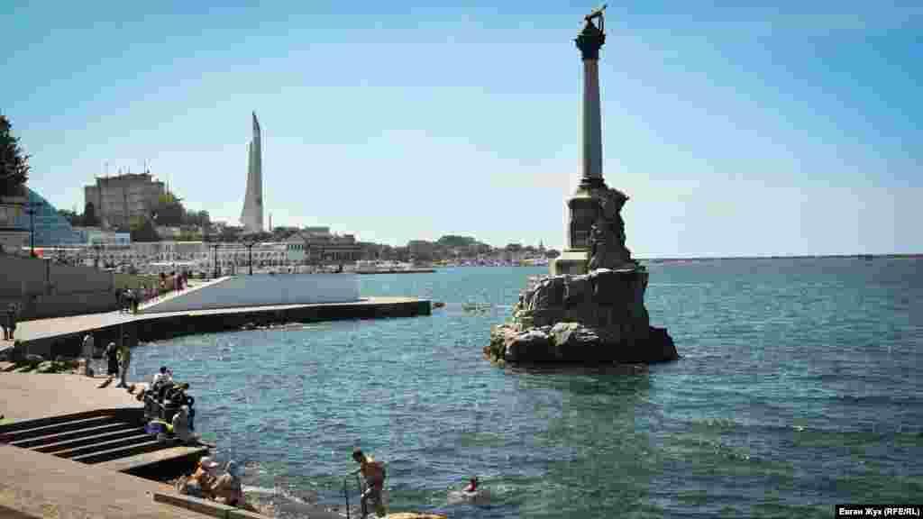 Некоторые купаются в море у памятника затопленным кораблям