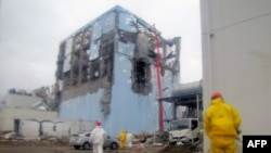 A Tokyo Electric Power Company handout photo of a worker spraying water to cool spent nuclear fuel at the reactor No. 4 building at Fukushima Daiichi nuclear plant (released on March 22).