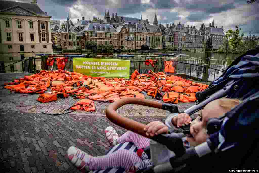 A baby in a stroller passes by life jackets displayed by the international antipoverty organization Oxfam Novib in front of the Dutch parliament in The Hague. The jackets serve as a visual reminder to the Dutch government of the suffering and risks hundreds of thousands of refugees have endured. (AFP/ANP/Robin Utrecht)