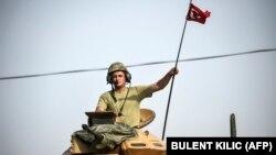 یک نیروی نظامی ترکیه در حومه جرابلس، پرچم این کشور را بر فراز تانک به اهتزاز در آورده است.
