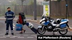 Женщина со своими вещами проходит мимо полицейского во время эвакуации жителей. Франкфурт, 3 сентября 2017 года.