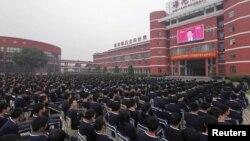 Қытай оқушылары биліктен кетіп жатқан Ху Цзиньтаоның сөзін үлкен экраннан көшеде тыңдап отыр. Қытай, Чжуцзи қаласы, 8 қараша 2012 жыл.