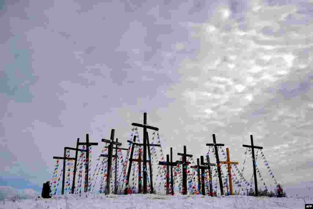 A woman prays on a hill with wooden crosses as she celebrates Palm Sunday in the town of Oshmiany, some 130 kilometers northwest of Minsk, Belarus, on March 20. (AFP/Sergei Gapon)