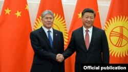 Kyrgyz President Almazbek Atambaev (left) meets with Chinese President Xi Jinping. Like other Central Asian leaders, he won't threaten key economic ties over ethnic brethren.