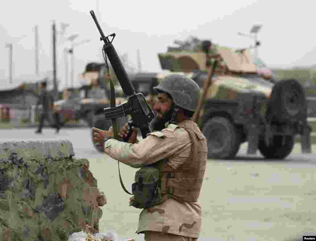An Afghan National Army soldier takes up a position at the site of the suicide car bomb attack.