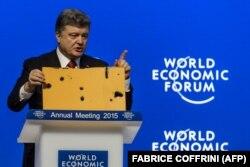 Президент України Петро Порошенко демонструє фрагмент пасажирського автобуса, який був знищений ракетним ударом російських гібридних сил на околиці Волновахи 13 січня 2015 року. Внаслідок нападу загинули 12 (за іншими даними, 13) людей, ще 18 були поранені. Давос, 21 січня 2015 року