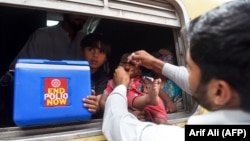 FILE: A Pakistani health worker administers polio vaccine drops to a child during a polio vaccination campaign at a railway station in the eastern city of Lahore on May 16.