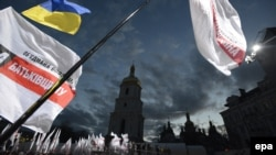 The flags of Joint Ukrainian Opposition wave above the crowd during their preelection meeting in front of St. Sophia Cathedral in Kyiv on October 26.
