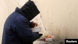Person i varfër duke ngrënë racionin e ushqimit të shpërndarë falas...