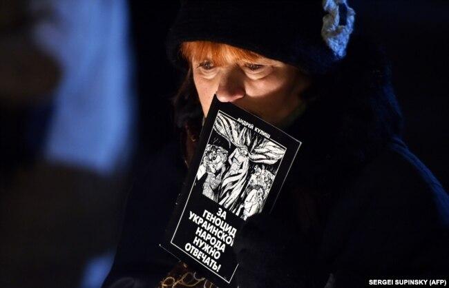 Жінка з буклетом «За геноцид українського народу потрібно відповідати!» під час вшанування жертв Голодомору-геноциду 1932–1933 років в Україні. Київ, 22 листопада 2014 року