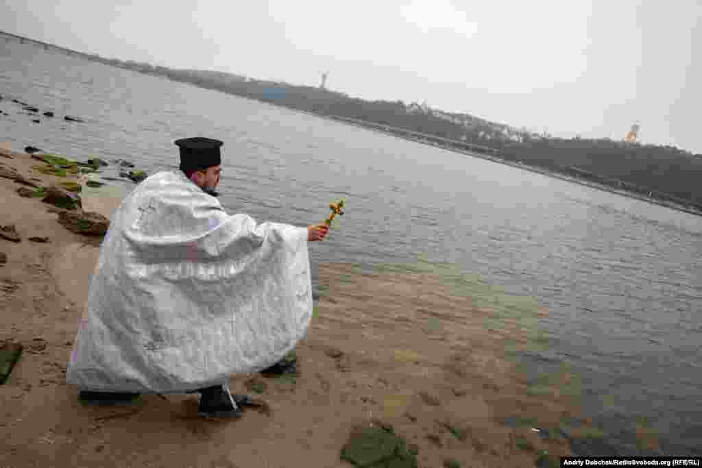 A military chaplain sanctifies the waters of the Dnieper River in honor of Ukrainian soldiers.
