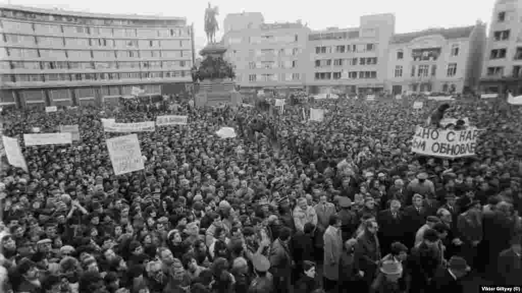 """Това е друг митинг. Той се провежда ден по-рано, на 17.11.1989 г., и по тази причина би трябвало да се нарича """"първи"""". Но в 30-те изтекли години той така и не се сдобива с този етикет.Организиран е от БКП веднага след като опозицията е съобщила, че ще се събира пред Св. """"Александър Невски"""". Тогава това не се разглежда като """"издърпване на чергата"""". Хората за първи път са участници в една съвсем нова публичност. Някои отиват и на двата митинга, и това изглежда съвсем естествено."""