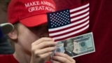 U.S. -- A child holds a '2020' US dollar bill with a picture of U.S. President Dinald Trump during Trump's 2020 re-election bid announcement in Orlando, Florida, June 18, 2019