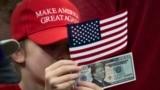 Дитина тримає доларову банкноту 2020 року з зображенням президента США Дональда Трампа