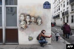 """Прохожая делает селфи на фоне портретов погибших журналистов """"Шарли Эбдо"""""""