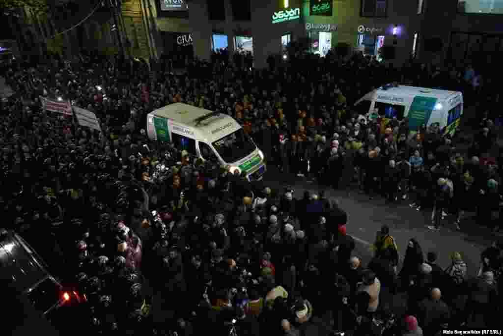 Машина скорой помощи едет через толпы протестующих в Тбилиси.