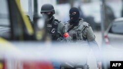 Belgium -- Police and special forces members patrol at the site of a shooting in Brussels, on March 15, 2016.
