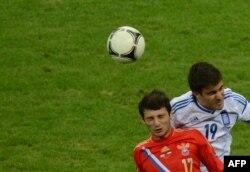 Слева направо: российский футболист Алан Дзагоев и член сборной Греции Сократис Папастафопулос. Варшава, 16 июня 2012 года.