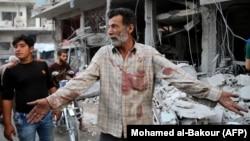Сириец в окровавленной рубашке возле обломков здания после о российского воздушного удара в районе Джишр-эш-Шугура, в провинции Идлиб, 25 сентября 2017 года