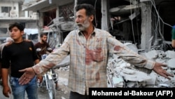 A Syrian man gestures near debris following a reported Russian air strike last month in Idlib Province.