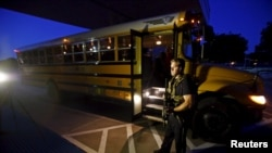 A police officer stands near a school bus used to evacuate attendees of the Muhammad Art Exhibit and Contest sponsored by the American Freedom Defense Initiative after a shooting outside the Curtis Culwell Center where the event was held in Garlan, Texas on May 3.