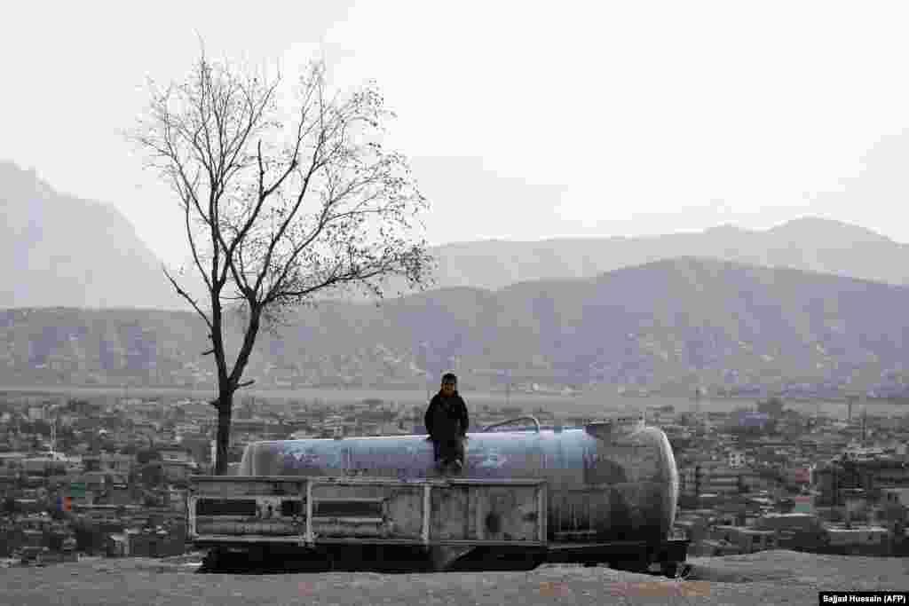 Аўганскае дзіця сядзіць на рэзэрвуары для вады на гары Надыр-хан у Кабуле