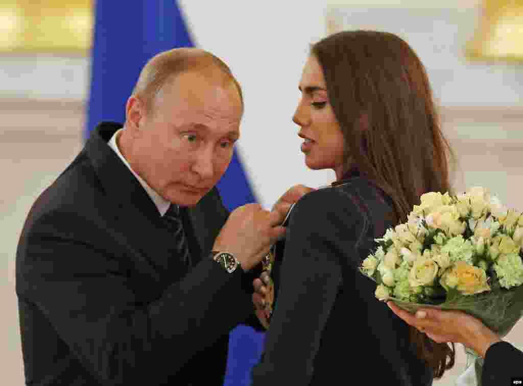 Владимир Путин и художественная гимнастка Маргарита Мамун во время церемонии награждения в Кремле. Август 2016 года.