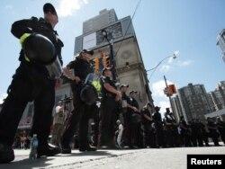 Полицейский кордон во время демонстрации против саммита «Большой восьмерки» в Торонто. 24 июня 2010 года.