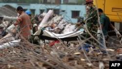 Құтқарушылар қираған ғимарат астында қалған адамды әкетіп барады. Бангладеш, 9 мамыр 2013 жыл.