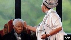 Оңтүстік Африка Респуликасының бұрынғы президенті Нельсон Манделаның маңдайынан әйелі ұстап тұр. Претория, 9 мамыр 2009 жыл.