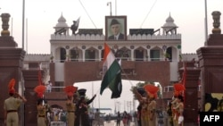 FILE: Pakistani Rangers and Indian Border Security Force personnel lower their respective country flags at the Beating Retreat Ceremony at the India-Pakistan Wagah border post.