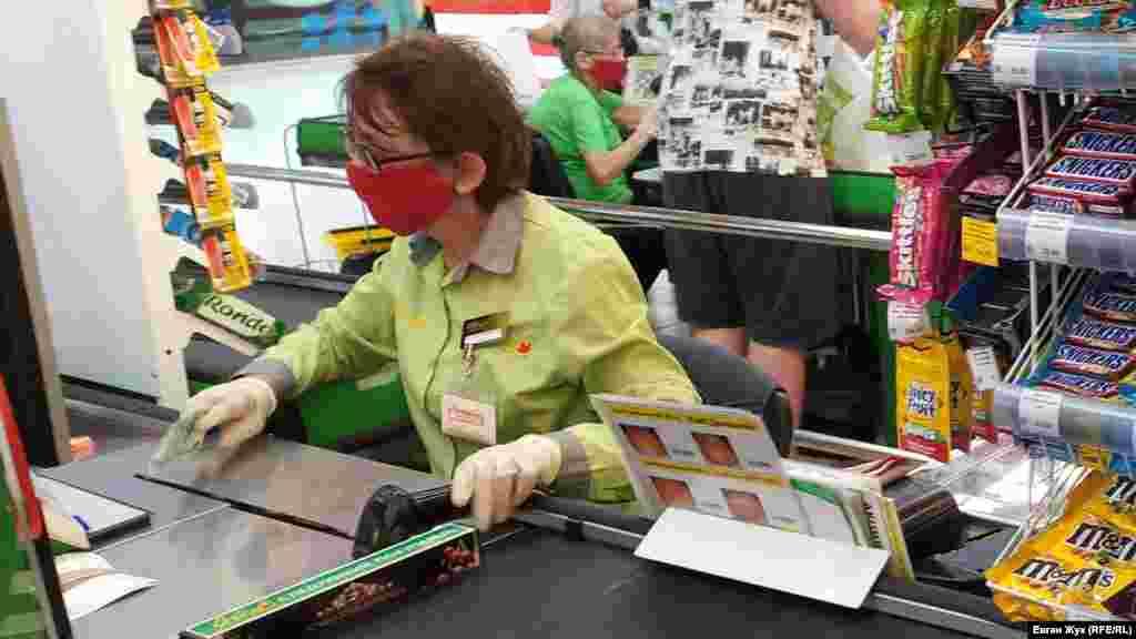 Продавці біля кас у торговому центрі – у захисних масках і рукавичках