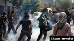 Iranian protesters run from tear gas at an opposition rally in Tehran on July 9