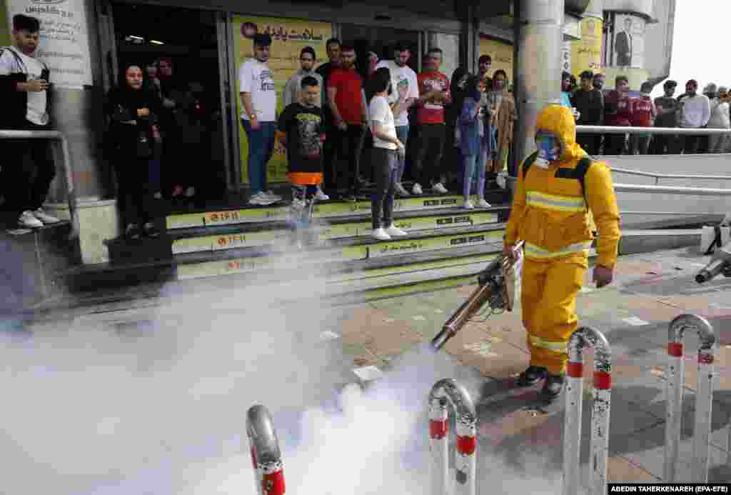 Iranians take pictures of firefighters as they disinfect streets in Tehran.
