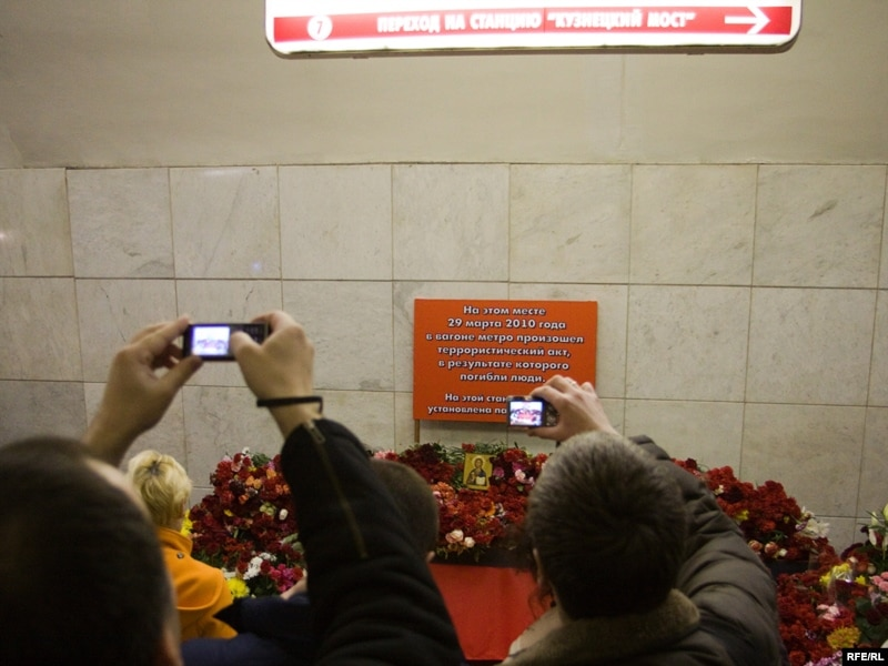 People lay flowers and candles at the Lubyanka metro station.