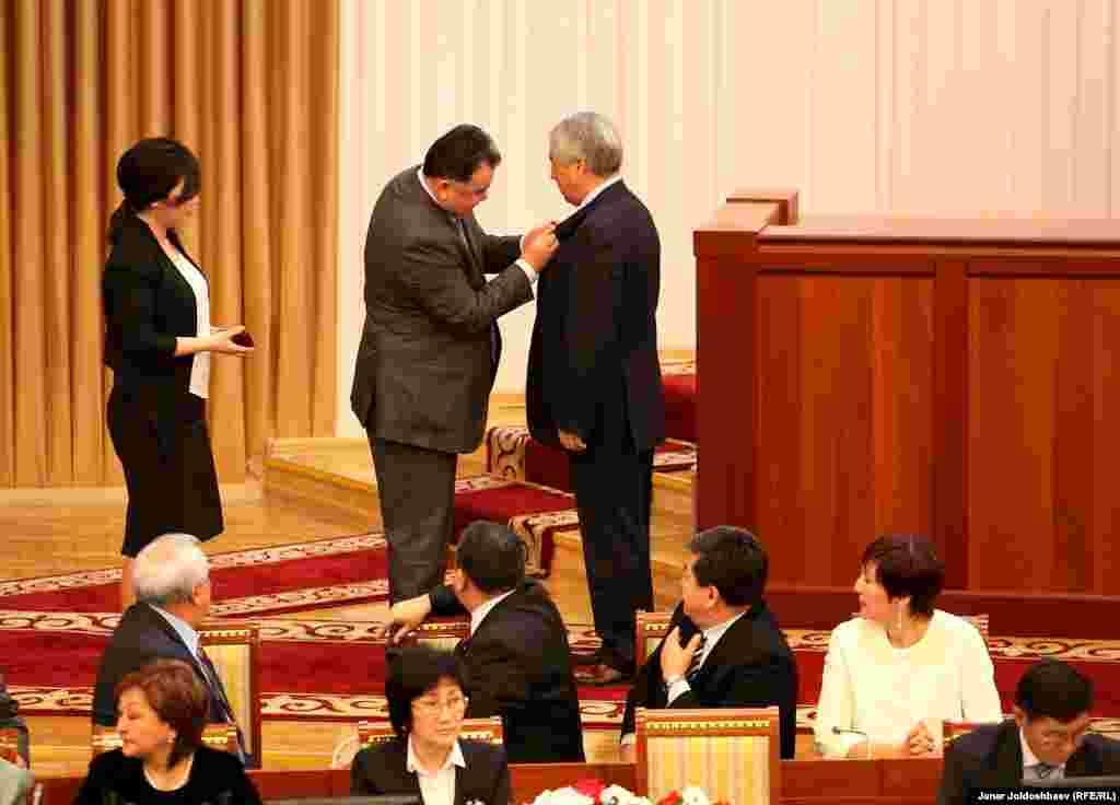 Председатель ЦИК Туйгунаалы Абдраимов вручает и одевает значок депутата Мыктыбеку Абдылдаеву.