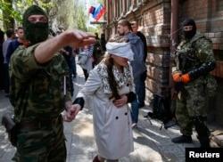 Проросійськи налаштований озброєний чоловік проводить українську журналістку Ірму Крат після прес-конференції у Слов'янську, 21 квітня 2014 року
