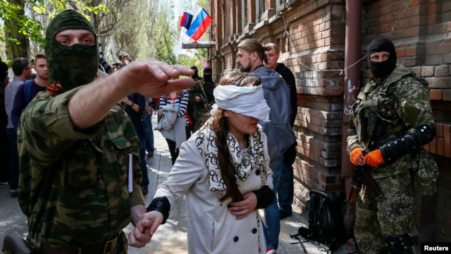 A pro-Russian fighter leads Ukrainian journalist Irma Krat away from a news conference in Slovyansk on April 21.