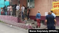 Люди стоят в очереди за лекарствами у оптечного скзала, Алматы, 1 июля 2020 года.
