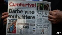 Мужчина держит в руках номер турецкой газеты Cumhuriyet.