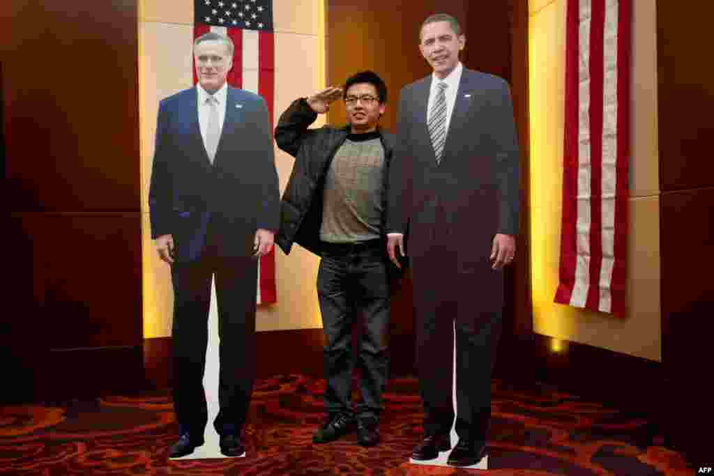 A man poses with carboard cutouts of U.S. President Barack Obama and presidential candidate Mitt Romney at a hotel during an event organised by the U.S. Embassy in Beijing.
