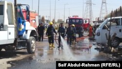 Firefighters clean the scene where two cars exploded in Kut on July 29, killing five people and wounding more than 30 others.