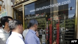 Iranians check exchange rates outside a bank in the capital Tehran. File photo