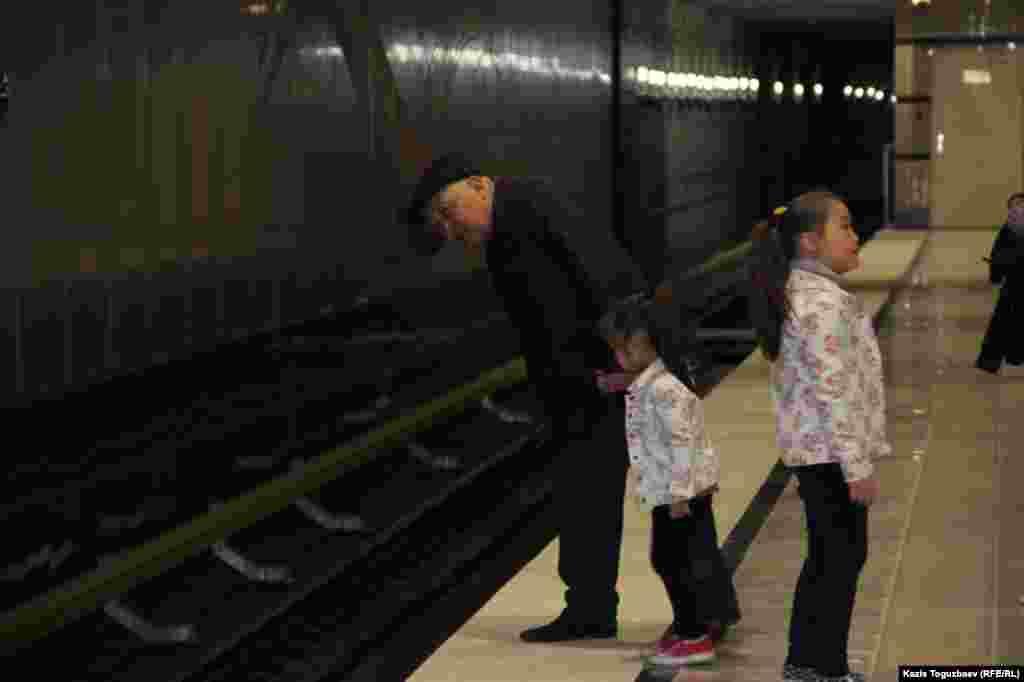 Мужчина на станции «Сайран» алматинского метро показывает девочке пути, по которым движутся поезда. Алматы, 18 апреля 2015 года.