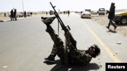 Libia: un luptător al unei facțiuni armate trage într-un elicopter rival.