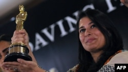 Pakistani director Sharmeen Obaid-Chinoy poses for photographs with the Academy Award she won in 2012 for a documentary on acid attacks on Pakistani women. Her latest movie tackles the subject of 'honor killings' in Pakistan, which she says claims the lives of hundreds of women every year.
