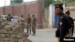 Полициячылар жана жоокерлер Дера Ысмайыл хан шаарындагы түрмөгө талибдер жасаган чабуулдан кийин уруш жөнүндө сүйлөшүүдө. 30-июль 2013