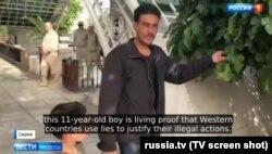 """Кадр из сюжета """"Вестей недели"""", на котором за спинами 11-летнего Хасана Диаба и его отца появляются российские военные"""