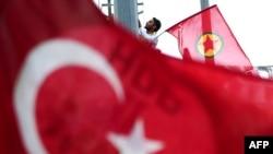 رجل يرفع علم حزب العمال الكردستاني خلف العلم التركي خلال تظاهرة في اسطنبول - 6 حزيران 2015
